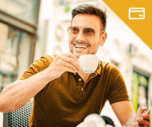 A young man wearing sunglasses sipping coffee