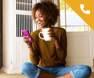 A young woman sitting on the floor looking at a smartphone and holding a mug