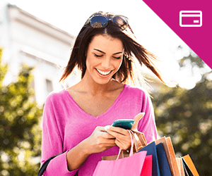 A young woman holding shopping bags looking at a smartphone
