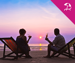 A couple having a cocktail while sitting on the beach during a sunset
