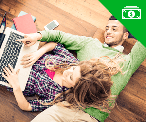 A young couple laying on the floor using a laptop